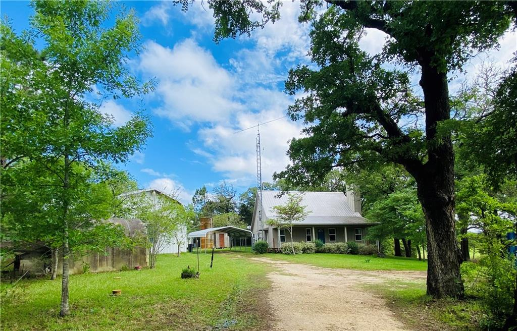 Fantastic views off this Farm House front full/deep porch and side deck! Take in the breezes and all this beautiful park-like country setting with its oaks & spruce/whispering pine tree grove, pastures, wildflowers, Green's Creek running through it at the back of the property & 2 ponds (can be well water filled in times of drought).  100% on well water with large concrete holding tank. The house well water is filtered and outside watering is unfiltered.  Reverse osmosis water available in the kitchen. The efficient house was meticulously constructed in 2009 with an engineered slab, standing seam metal roof, hardi-like siding, 3 to 4 bedrooms (2 on the main floor), island kitchen, cathedral ceiling in the family room & lots of storage.  There is also an underground concrete storm shelter, a well house & storage building. The almost 900 sq foot barn is a strong trussed/pole construction on a slab with metal roof. has a loft area (no railing!), has a side entry garage door & was plumbed for a bathroom.  There are two separate 2-car carports. There is a 1972 mobile home of no value, but utilities are in place for electric/septic. Trees include persimmons, oaks, redbuds, hickory-pecan 'hickan', willow, pines, cedar, spruce, elm +.  There are also purple irises, a prolific mustang grape arbor by the house and a lot of dewberries around.  There are deer, wild turkeys, occasional wild hogs, squirrel & many bird varieties. Agent related to sellers. Call agent for showings. Offer cut off is Wednesday 5/5.