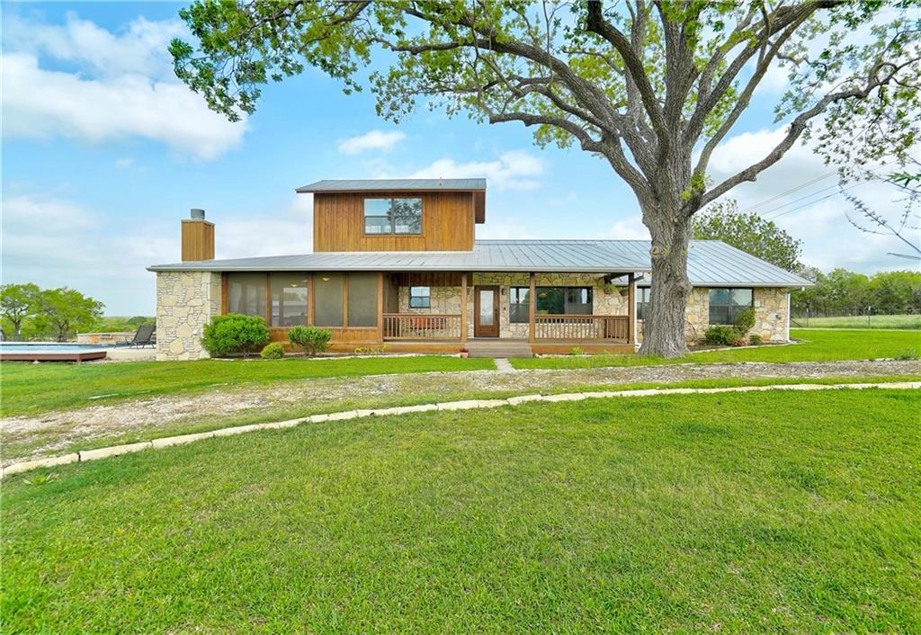 Gorgeous opportunity to own a beautifully remodeled home on just over 7 acres, centrally located, with livestock barns, a swimming pool, professional grade appliances including a large island. A wrap around screened porch with fireplace, perfect for entertaining. The barns include  3 horse stalls and a tack room.  Also included on this unique property is a 3 bay metal shop with concrete floors. There is a well used for irrigation. The upstairs can be a home office setting or a flex room.