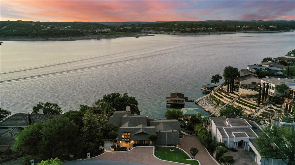 """Welcome to 1211 Challenger – an entertainer's waterfront dream home on Lake Travis. When you visit you quickly realize that this is one of the most interesting homes on the lake. The approach is welcoming with a gorgeous stone tiered entry from the abundant guest parking. The floor plan cascades down the cliff on 3 levels with oversized rooms offering comfort on a grand scale. The neutral interior nods to the 80's with a contemporary vibe provided by the wood ceilings, stone walls & Saltillo tile floors - perfect for a relaxed lake lifestyle. The current owners have lovingly invested over $230,000 in recent upgrades elevating this home to its next chapter. A perfect gathering spot is found on the second level at the kitchen that overlooks the main living room. Privacy & accommodation is in excess at all of the bedrooms and baths including a huge """"bunk room"""" with en-suite. Three uniquely different living spaces offer plenty of room for everyone. Journey outside to the multi-level decks & soak up the panoramic views. The lakeside is beautifully landscaped with mature trees, waterfall, a gazebo & meandering staircase down to the oversized dual dock to house your boat & jet skis. Come see what true lake living is like in the famous Texas Hill Country. It's all waiting for you here in Lakeway."""