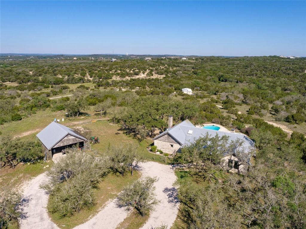 This ~107 acre ranch just outside of the Dripping Springs City Limits with no deed restrictions features 5 rentals currently producing $5600 monthly income. The main home features a 3 bedroom, 2 bath ranch home with spectacular views!!! Living room offers beamed ceilings, great natural light and oversized fireplace. Hardwood floors throughout.  Fireplace, tall beamed ceiling and views in primary bedroom. Enjoy a 600 SQFT private gym just minutes from the main home.  Clubhouse has the potential to be 2 additional leased properties. There is an additional 3 story home that is at frame stage with some electrical that has corporate housing or Air BNB potential.  Easy access to HWY 290 with a traffic light.