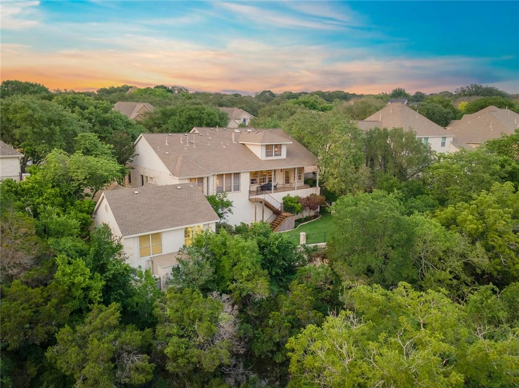 Unique .44 acre Northwest Austin property featuring a 2-story, stone home overlooking a lush lawn and wooded enclave with spring-fed creek and showcasing panoramic views of the adjacent Trailhead Park. The 2000-build Jim Rado custom home sits on a quiet, horseshoe street and is located just 1 mile from A-rated/IB Spicewood Elementary School. Zoned to acclaimed Round Rock ISD schools: Spicewood E/Canyon Vista Middle/Westwood High. Primary Suite plus two additional beds and a full bath on main floor means multi-generational living! Open floor plan with high ceilings and crown molding. Gas cooking. Large, covered porch located off the kitchen offers sunset views above the treetops. Downstairs living and primary suite wired for sound. HUGE walk-in closet in primary bedroom also includes IT control center. Dedicated, light-filled office for work-at-home. Large, private suite upstairs with living area, full bath and bedroom #4. Not one, but two, 2-car oversized garages. Detached garage is plumbed for water and air compressor--perfect for auto enthusiasts. Engineered, rebar-enforced rock wall separates lawn from enclave with a custom-designed stair leading to a wooden deck nestled among the trees and creek. Over 600 sq ft of attic and stone outbuilding storage. Private golf/tennis club community, social club with pool, kids' swim team. Golf cart-friendly streets! Ask Agent about complimentary social Club Membership. Easy access to 183 Tech Corridor, Mopac and 360. Special financing available.