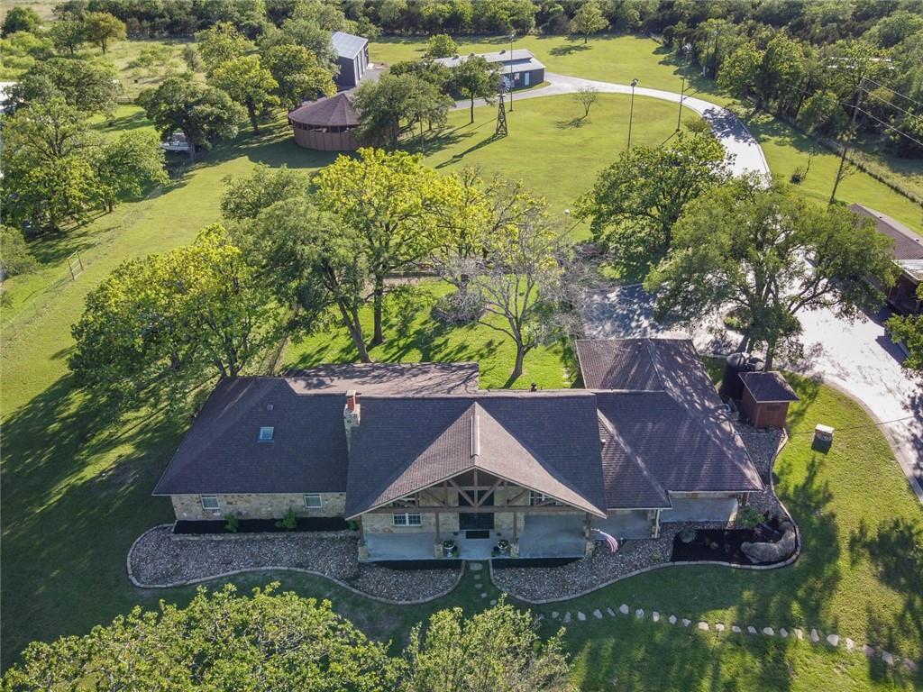 Rare and unique property for any hobbyist, enthusiast, collector or animal lover on 5 beautiful acres with many established oaks across from the Williamson County Park. Property features a main house, round party barn, and TWO 40x90 incredible workshops; one with a separate mother-in-law suite! Acreage is fully fenced with decorative and game-type fencing along with a private gate. Main house is 3 bedrooms, 2.5 bathrooms with 2 car attached, 4 car detached garage and carport that could fit an RV. Built in 1979 and fully renovated in 2008! This open concept home stuns the eye with 16' wood ceilings in main living areas, tile and hardwood flooring throughout, plantation shutters, and a beautiful wood burning fireplace. Kitchen has a luxury full-size stainless fridge, 6-burner gas range, and built-in bar area with wine fridge! Main bathroom has large walk-in shower, jacuzzi tub and dual vanities. Round Party Barn has phenomenal acoustics, light system and stage for bands. Shingles replaced on detached garage, party barn, and house in May 2021. Shop #1 is heated/cooled and includes full 1 Bedroom apartment with full kitchen, built-ins, 3/4 bath, plus laundry area. Powered roof vents, oversized garage door for RV parking/storage, reclaimed wood walls, and enough space to fit roughly 15 cars. Shop #2 was built in 2017and shares 20,000-gallon rainwater system as well as a septic system with Shop #1.  Shop #2 includes a 2nd story loft with 3/4 bath, kitchen including fridge, sink, and microwave.  This shop is heated/cooled by two 5-ton HVAC units, and features compressed air lines, projector with screen, 2 post car lift, and enough space to park around 18 cars.  Horses Allowed!  Please note the bedroom/bathroom and square footage count includes the guest house in Shop 1. Keywords: Barndominum, Bardo, Livestock, Man Cave, She Shed, Pasture, Barn, Workshop, Casita