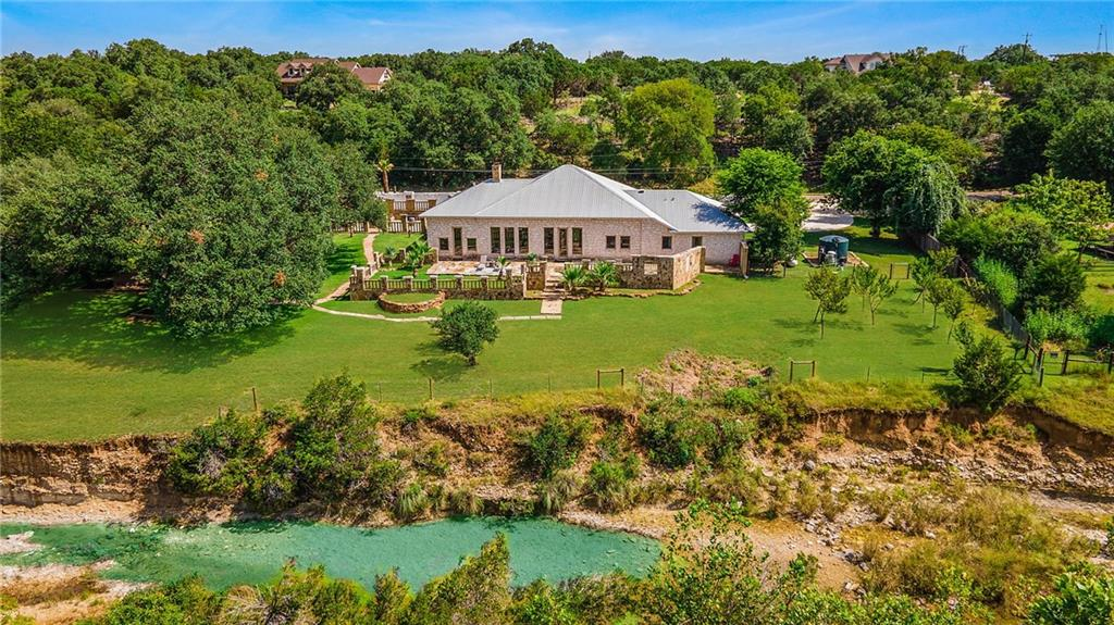 """This spectacular home in the heart of Dripping Springs is a rarity, to say the least! With the custom stone, beautiful tile work throughout the house, and elegant finishes, there is no doubt that you will fall in love with this immaculately presented home. The home is behind a lovely 6-foot stone wall for privacy. Right when you enter this truly open concept ranch-style home, you will find an oversized great room with 20' high ceilings, travertine floors, and enormous wood beams which are supported by limestone columns. You'll find your master suite to your right, and the two additional bedrooms are on the opposite side of the great room. The magnificent lighting throughout the home compliments the stylish travertine tile flooring and granite countertops in a large chef's style kitchen. This property is the definition of modern elegance! Panoramic windows, 8-foot wide natural stone fireplace, and tall doors (10' tall) in the common area just add to the elegance of the home. The walls are at least 20"""" thick and the home is very well insulated. The two oversized natural stone patios, outdoor wood-burning fireplace, a large limestone slab picnic table, and beautiful old oak trees give this residence a tranquil and serene vibe. With over 300 feet of frontage along Barton Creek and 1.5 acres of park-like grounds, it is an excellent place for friend/family gatherings. Located in the award-winning school district of Dripping Springs, you don't want to miss the opportunity to own a piece of heaven that seems so far but is still so close to everything you need, including shopping, Hill County's best wineries, breweries, distilleries, and restaurants."""