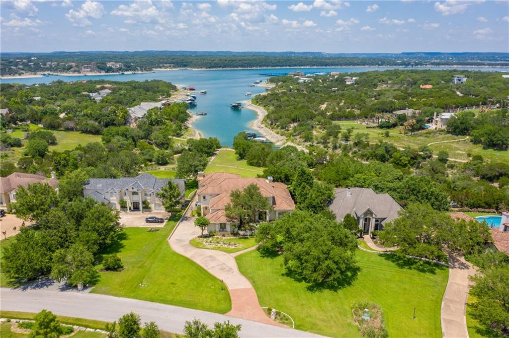 Lovely waterfront estate home beautifully appointed at the end of a large cove overlooking Lake Travis. This gorgeous custom home is nestled on 1.316 manicured acres in the prestigious Coves of Lakeway. Inside, you will be welcomed with custom finishes throughout that include designer lighting, imported Cantera columns, travertine flooring as well as hand scraped wood flooring, custom cabinetry and so much more. Designed to fully enjoy the Lake Travis lifestyle, nearly every room in the home offers big water views. The main living area features 22 feet high soaring ceilings, an oversized stone fireplace and a huge 2 story picture window to take in the fabulous views. The spacious private master suite is complete with a stone fireplace, sitting area and patio access. Huge master bath with dual vanities, oversized walk-in shower, jetted tub and large walk in closet. Chefs kitchen with high end appliances and custom solid wood capped center island. Temperature controlled Wine Room, Media Room, Game Room and large Study too! Plans for pool are also available. Coves of Lakeway residents enjoy their own community day dock located close by. Walk to Lakeway City Park. Lake Travis Schools. Minutes to shops and restaurants.