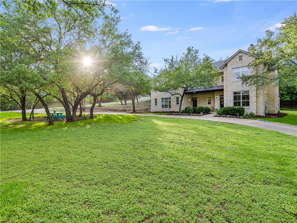 Impressive Farmhouse Traditional custom home on 1.38-acres surrounded by the incredible beauty of Texas Hill Country. The residence is presented on a sprawling lot with a long circular driveway and majestic Oak trees that provide both shade and privacy. The gorgeous stone exterior with natural wood accents and natural landscape grounds set the standard for the home. The high ceilings, beautiful archways, and abundance of natural light welcome you as you step into the formal entry. The private home office with his and her executive desks, double-sided fireplace, crown molding, and large windows with plantation shutters is sure to impress. A spacious living room with built-ins, a wall of windows, and a cozy stone fireplace flows effortlessly into the expansive kitchen with a wrap-around breakfast bar, an abundance of cabinetry, a built-in refrigerator and oven, and an electric cooktop. Gorgeous archways bridge the kitchen and formal dining room which features a custom built-in buffet and large picture window with an exceptional view. The owner's suite is wrapped in windows that overlook the greenbelt and offers a spacious en-suite with a double vanity, decorative framed mirrors, a walk-in shower, and his and her closets. The second and third bedrooms are generously sized and share a Jack & Jill bathroom. The fourth bedroom has a walk-in closet and direct access to the guest bathroom - perfect for guests or in-laws. A large game room with a walk-in closet completes the second floor and could also be used as a fifth bedroom. Relax under the covered back patio while sipping your morning coffee and soaking up the beauty of nature. Enjoy outdoor living at its finest with plenty of space to create your dream backyard! You can easily add a sparkling swimming pool, outdoor dining area, and more! This property is conveniently located to all that Austin has to offer while feeling a million miles away in your own oasis.