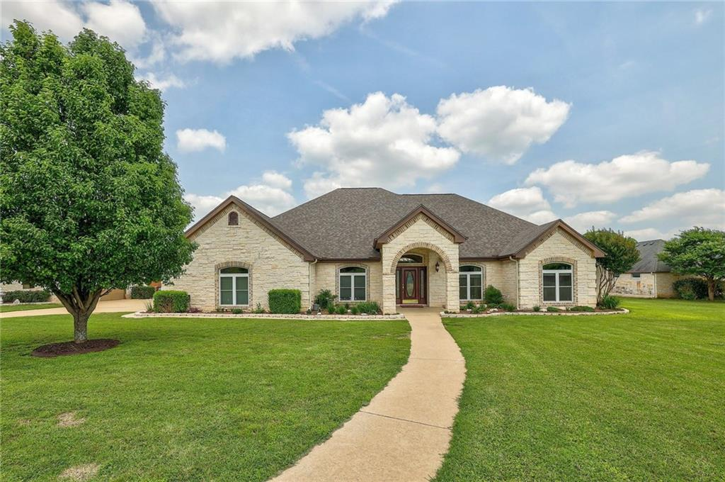 Living is easy at this stunning & IMPECCABLY maintained ranch style home in the highly desired Gabriels Overlook! Nestled on a sprawling and private 1.38-acre manicured lot - just a short walk away from the San Gabriel river! This home has beautiful architectural features including tray ceilings, large windows, & more. The open-concept floor plan flows effortlessly & incorporates a family room, formal living room/dining room or study, expansive kitchen, a spacious owner's suite, & three generously sized secondary bedrooms. The family room offers a wall of windows w/beautiful views of the greenbelt & a cozy wood-burning fireplace; and is open to the kitchen & breakfast area so entertaining family & friends will be a breeze. The impressive kitchen offers an abundance of cabinetry for storage & counter space for prepping meals & boasts sleek granite countertops, a tile backsplash, crown molding, electric cooktop, & built-in oven. The owner's suite is large with crown molding, a tray ceiling, a walk-in closet with a storage system, & doors that lead to the extended outdoor patio. The second & third bedrooms are generously sized & have nice size closets. The fourth bedroom has a walk-in closet and an en-suite - perfect for guests or in-laws! Relax under the covered back patio & soak up the Hill Country views, watch the stars, and enjoy the peaceful sounds of nature. Entertain friends & family in the expansive backyard complete with an outdoor kitchen, hot tub, & fire pit. Community restrictions allow for the addition of a guest house, pool, workshop, & more! Take a short walk to the San Gabriel River & wade,fish, walk the trails, or cross over into Garey Park! In addition to the attached 2-car garage, there is also a detached 2-car air-conditioned workshop with extensive storage cabinets, shelving & a second-story loft for your toys & hobbies. Pride of ownership shines in this home! (2021 roof, 2020 Pella vinyl windows, recent water heater & SS LG appliances).