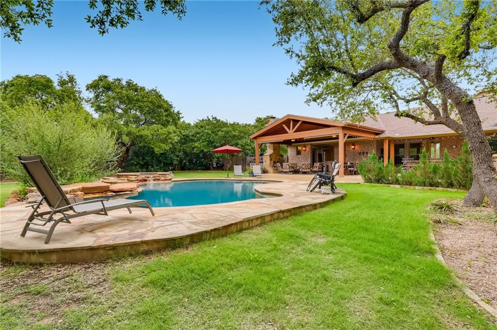 """Country Estate on nearly 5 acres in Dripping Springs off of Fitzhugh Rd. in the Lone Star State's beloved Texas Hill Country. Located on a very quiet street with easy access to Austin and Dripping Springs. Highly desirable flat lot with plentiful mature oak trees. Beautiful private pasture view with spectacular Texas sunsets. 2 Horses and other animals allowed with minimal restrictions. The property backs to a hundred-acre ranch giving you the ultimate privacy. The lovely 6854 sq. ft home will not disappoint with its 5 ensuite bedrooms featuring 2 primary bedrooms on the main level. It has a wonderful open floor plan with soaring ceilings and fantastic natural light. The true chef's kitchen has 2 center islands and abundant storage plus stainless steel appliances. The kitchen overlooks the beautiful backyard pool, spa, outdoor kitchen, wood-burning fireplace, and pavilion. Not only does the property have its own 55,000-gallon rainwater collection system with a top-notch filtration system it also has a 750 ft. water well. This property could easily become """"off the grid"""". It has numerous possibilities to meet your needs. There is so much indoor and outdoor space for adults, children, and animals, not to mention you could plant your own orchard, vineyard, or very large garden. What an amazing one-of-a-kind opportunity! Dripping Springs Schools are exemplary and the Dripping Springs High School is rated as a Recognized High School by the Texas Education Agency on the Academic Excellence Indicator System."""