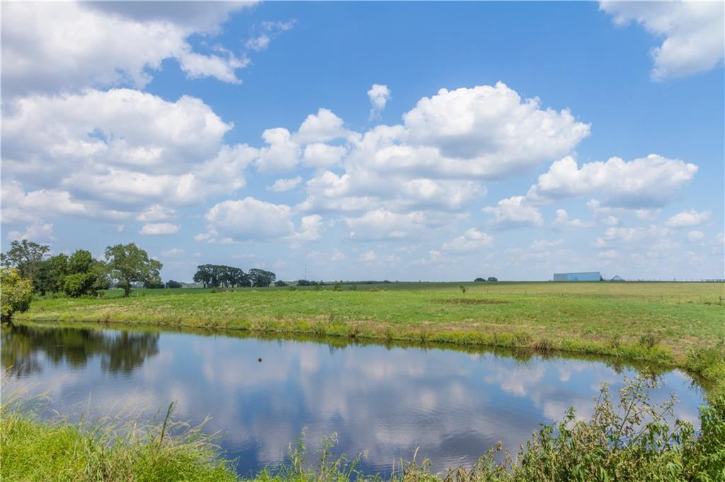 Stunning panoramic views of rolling pasture; improved pastures with large equipment barn, old farmhand house (unknown septic, not habitable as it), ponds, chutes and runs for cattle. Electric in place. Owner flexible on restrictions.