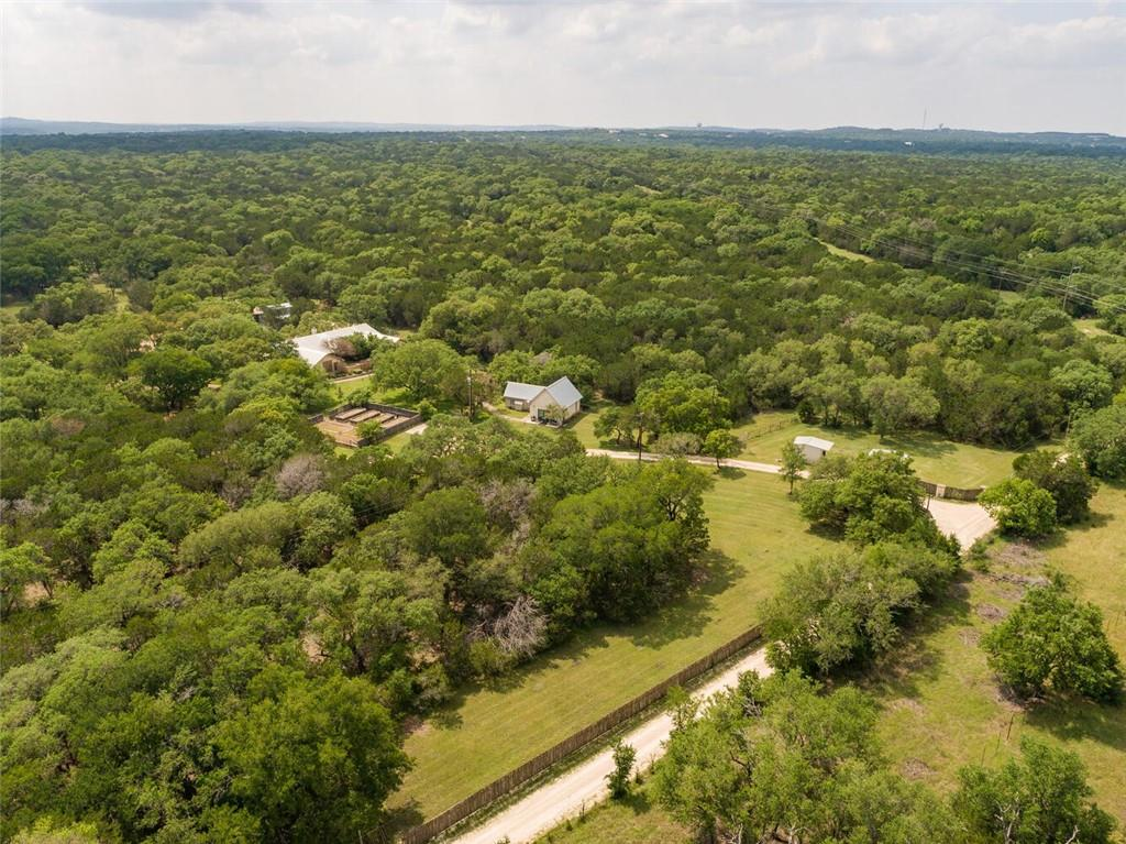 Enchanting and rare Hill Country estate on nearly 17 UNRESTRICTED acres. This property is comprised of two tracts: one 5.01 acre homestead tract plus an agriculturally exempt 11.86 acre and they provide an idyllic setting for the owner wanting privacy, freedom under big Texas skies. Gorgeous lush land (ideal for agricultural, commercial, equestrian or development purposes), majestic oaks, a beautiful custom home (approx. 3016 SF, 3 bed/1.5 bath--owners have design plans for an addition of 1200 SF), pool and spa, a lovely courtyard, detached VRBO guest house (3 bed /1 bath, 989 SF--leases for $2500/month or $175/night), large barn/workshop w/adjacent 1500 SF pad for future barn/workshop extension, garden and plenty of space to enjoy for residential, agricultural or commercial purposes. Small- town feel but mere minutes to Austin and all the beloved local attractions of the Texas Hill Country.