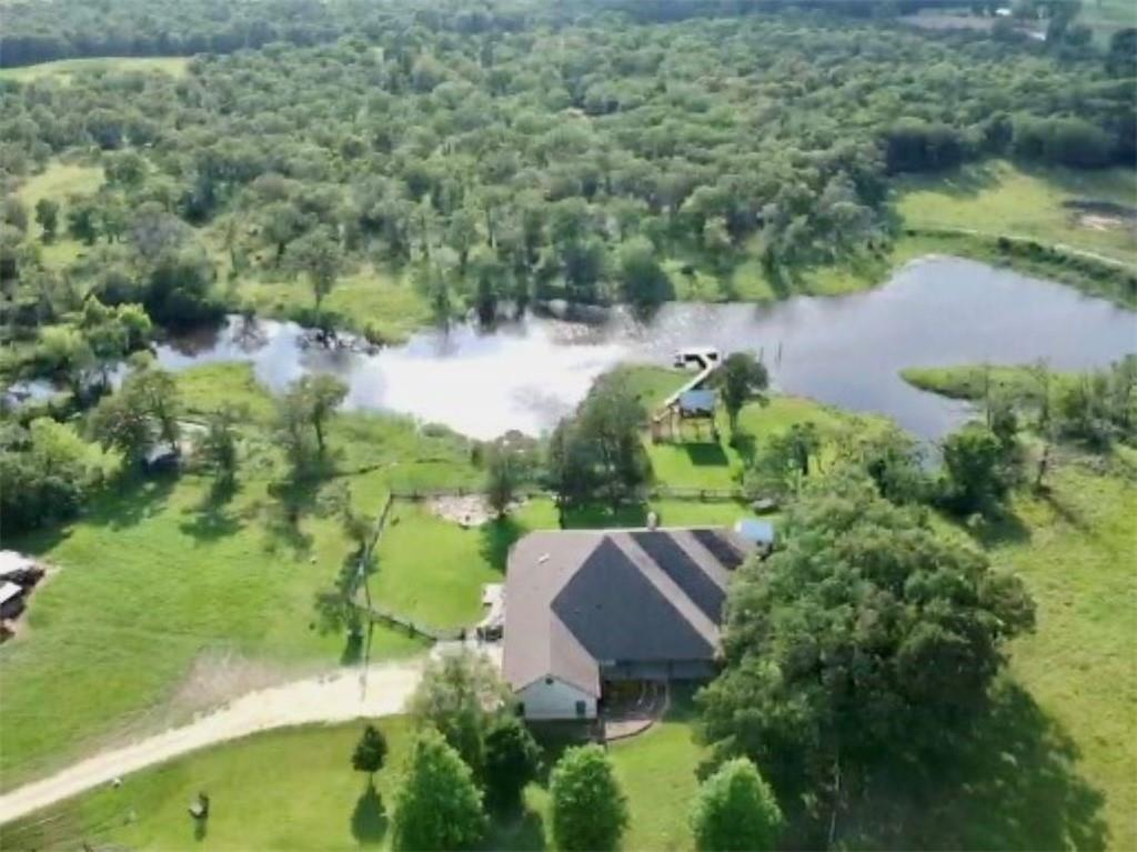 Absolutely a Must See!  This is a beautiful 125 +/- acres with a magnificent 3/3.5 3133SF Stone home and precious 1/1 guest house in Lee County.  The main house kitchen sports SS appliances, silestone countertops with brick backsplash, large island with eating bar and rock accents.  The living space is open with wood stove, crown molding, and rock accents.  The dining area is lined with pristine large transom windows to let in light and view the beautiful landscape. Large master bedroom is spacious and has a unique dual master bath complete with claw-foot tub and walk-in shower. Relax in your rocking chair on the spacious front and back porch with great views of the 5 ac lake, or cast a line from the fishing pier nearby.  The precious guest house is one your guest won't want to leave with full kitchen, living, bedroom and bath.  Read your favorite book in the treehouse overlooking the lake or enjoy your favorite hobby in the she shed.   The property is a working cattle ranch that has a slight roll with various native and improved pastures, barn and sheds.  The pastures are fenced for rotation, organic ranching.   This is an amazing property that you need to see to appreciate.