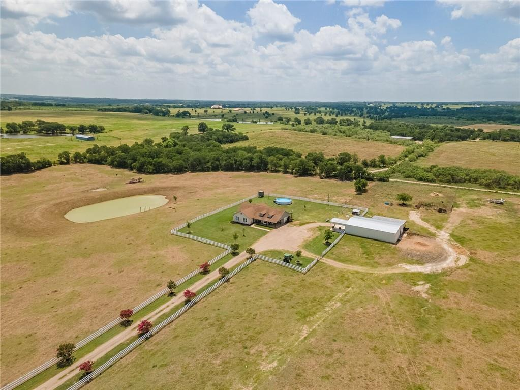 Less than an hour from Austin/30 min to SH 130 Toll. Simply Breathtaking with pristine hilltop views with vibrant fuchsia pink crepe myrtles make a stunning statement against the bright white of the picket fence. This remarkable 26.59 acres you just have to see with your own eyes is AG Exempt with chutes and pens & ready for your horses, cows, and kids! Large metal Barn is 40 X 60 with 40 X 20 concrete area that is also partially covered provides protections for tractors and equipment. Not only is the land amazing but comes with this beautiful 2,640 sq. ft. home with  4 Bed/2 Bath with plenty of storage and closet space throughout with custom built in cabinets. Beautiful, Panoramic Views from every window in the house! This open concept floorplan has a Gourmet Kitchen with Granite countertops and stainless steel appliances, magnificent great room with high beamed ceilings plus a dining room, kitchen nook, and plenty of island seating at the bar for the entire family.  Come escape all the noise and bustle while enjoying your view of the pond & the cows grazing on the rolling pasture from the large, covered porches. This house was made for outdoor dining, wildlife watching or just chilling! Enjoy Paradise & Privacy in the popular Thorndale ISD. This is the place you dream about!