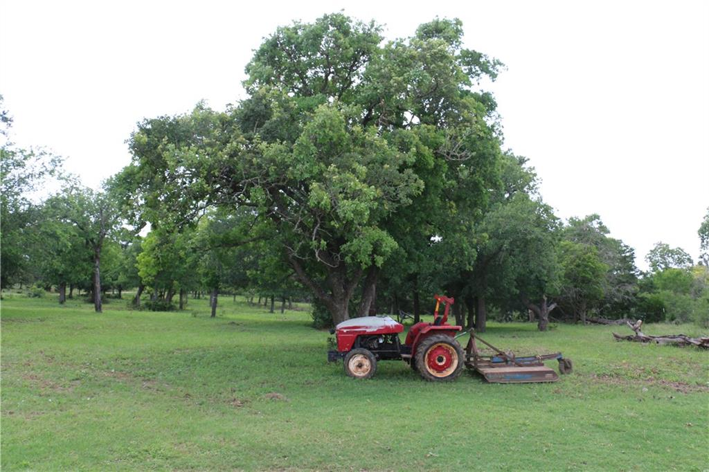 Own your own beautiful slice of Texas in this 11+ acres. Unrestricted land waiting for a new family to enjoy the country life This beautiful acreage holds so many possibilities for a family to enjoy by themselves or add other homes as the layout of this land offers that opportunity. Included. a sweet 1800 sq ft home sits in the middle of this tree laden acreage.  3/2 home boasts a split floor plan and an open concept. The beautiful kitchen island complete with a farm sink over looks a large family room.  Eat in kitchen and open concept are perfect for entertaining.  Enjoy large primary bedroom complete with on suite which contains a spacious walk in separate shower, a garden tub and dual vanities.  Both secondary bedrooms have large closets.  Enjoy the out doors... have a BBQ under the large oak trees, tend to your chicken in the ample coop. or just walk the beautiful open pasture. The clearing around the gorgeous trees is like having your own park. ***** Bonus...this property is complete with a full RV hook up. Quiet country living at its best.