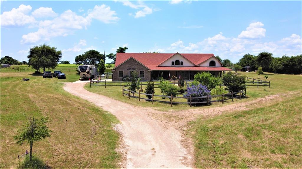 """Your farm & ranch property awaits you! Incredible custom built home (details on separate sheet) on 24 AC w/2 water tanks (= approx 1.5  pond ac). 3 sep fenced pastures for horses or cattle. No-climb horse fence, barbless wire & barbed wire on E property line. Includes a 60 ft. round pen. Cedar post & plank across front on Hwy 36. Dbl gate w/ 90 ft sally port to prevent livestock escape. Outer gate has mechanical gate opener. Hay cut every yr between 10-70 round bales, depending on rain that yr. Hay is Bermuda & native TX grass mix. AG exemption. 48'x36' metal barn w/3 main compartments. 1 bay stores tractor w/implements, 1 for 42 ft 5th wheel RV in center (14.5' clearance) & last 2 stalls w/paddock. Barn has water run to W corner to water livestock in smaller pasture. Outstanding dove hunting & ducks use ponds as stop overs during duck season. Rabbits are plentiful. E wall of house off gar set up for RV storage w/50 amp plug, water spigot & grey/black water dump pipe. Landscape includes sodded Tifton yard, peach, plum, apple, pear, fig, pecan & assortment of other TX trees. Highly fertile garden is established in back yard area & is fenced. A chicken/rabbit/duck enclosure is located at the rear property line. Variety of regionally tolerant plants & bushes in both front & back yards. Fence for yard around house & traffic circle is treated wood 4x4s set in concrete w/treated decking boards. FULL PRICE makes this turn key & ALL conveys except personal property! 55 hp 4x4 John Deere tractor (2011 model) w/7' shedder, hay fork, bucket loader, 3-pt posthole digger w/9"""" auger & a 65 gal sprayer w/12' boom. Riding lawn mower & a Razor.(See sep list) Back patio includes 10x14' pergola sits on concrete slab, w/CF, lights & plastic roof panels for weather protection, roll down sunscreen on W side. 5 person hot tub w/new filters, off French drs of master bedrm, also covered by pergola w/plastic roof panels & festive lights. Front porch w/large sitting area which overlooks ponds"""
