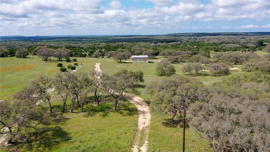 This property is Breathtaking! Must SEE! This is located at the highest point of the subdivision. Lots of huge oak trees, rolling hills, views, pond, huge 40' x 50' x 14' metal shop, with 5 bay roll up doors. Shop is completely roughed in and ready to be connected to water and septic. There is a 3000 gallon rain water collection system in place, as well. (200 amp breaker box installed in the shop and wired with an RV plug) Electricity is on the property with separate meter for the shop and house, when ready to build. High speed internet is available. Working beehive box is included on the property. This shop has a framed in room and bathroom and could very easily become livable. Well and septic needed. Don't pass up this opportunity to own some of the prettiest land in The Hill Country!
