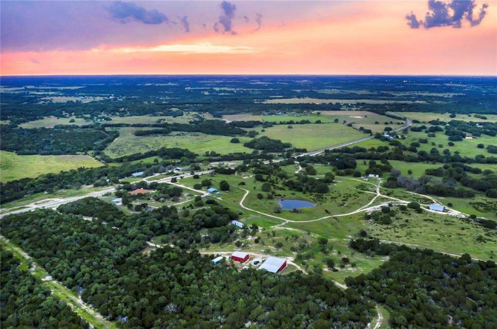 An incredible opportunity to own a blank canvas ranch in the Heart of the Hill Country, less than an hour to downtown Austin.   Come and build your dream home, well, electricity and septic already in place.  The ranch is 100% high-fenced in good - very good condition with an automatic gate at the main entrance.   - The ranch features a barndominium with wonderful view of the hill country, cabin, mobile home, large barn with walk-in cooler and rail system for game, a lean-to for storing equipment, a pond, and seasonal creeks. - Wildlife includes: Improved genetic whitetails from South Texas, Axis, Blackbuck Antelope, native turkey and dove. - Please ask your agent for a detailed list of improvements