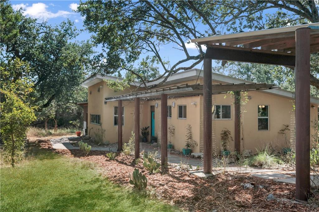 If you're looking for unrestricted private secluded living, this is it! Full time home, weekend retreat, or family compound - you can do it all here. Lots of privacy - fully fenced and heavily wooded acreage with lots of beautiful oak trees. Very energy efficient home with ICF (Insulated Concrete Forms) constructed walls, SIP (Structural Insulated Panels) roof, and 7.28 KW Solar Panels, grid tied, which keeps electric bills very low.  Rainwater is harvested off of the house and carport roofs with approx. 28,000 gallon rainwater collection system.   There's also a separate well, a barn, and some open grassy areas mixed in with the wooded acreage. Beautiful contemporary design with open floor plan. Amazing large covered rear porch overlooking an outdoor tree-covered sitting area. Current owner liked things natural and it shows with lots of native grasses and plants throughout. There's a wet weather creek and lots of room to roam or space to add additional buildings.  This is a very unique, difficult to find property.  Custom designed and built to the owner's requirements by Z Works Design Build, it wouldn't take much for a future owner to live off-grid if they so desire.