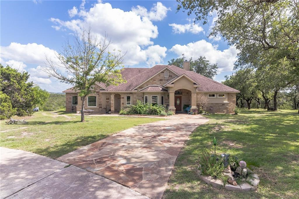 THIS CUSTOM BUILT 100% STONE/STUCCO SINGLE STORY HOME ON 13+ ACRES IS SURROUNDED BY NATURE & HILL COUNTRY VIEWS! Recently added Andersen windows allow for an abundance of natural light inside while providing great Hill Country views out of almost every room in the home! The open formal living & dining area leads into the kitchen w/breakfast area & family room. The well appointed kitchen offers granite counters, stainless appliances, pantry & loads of storage space. The spacious primary suite has tray ceilings, double vanity, walk-in shower, built-in cabinets, & an exterior door to access the rear patio. There are three additional guest beds on the opposite side of the home (two w/a Jack & Jill bath). The 30'x50' garage/barn w/large sliding doors on each end is perfect for storing your cars, boat, lawn equipment and more. VERY LIGHT RESTRICTIONS ALLOW FOR COMMERCIAL USE & WOULD BE IDEAL FOR ANYONE WANTING TO HAVE THEIR HOME & BUSINESS ON THE SAME PROPERTY. Recent updates include windows, limestone walkway & side patio, new granite counters, water heaters, A/C, and more.