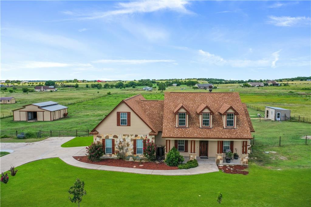 Welcome home to country living at its finest with this equestrian estate! Low county tax rate of 1.86% and current ag exemptions in place. This gorgeous 4 bed, 3 bath home sits on 5.11 acres of open land and features a horse barn with 4 stalls and an office/tack room.  Water and electricity in the barn.  Pasture is completely fenced and cross fenced. RV hookups on the property with electricity and dump station for visiting friends. Impressive entryway welcomes you with high ceilings, a stone fireplace, and an open layout for easy living. Spacious primary suite features tray ceilings, a garden tub, a large tiled, walk in shower, and dual sinks - perfect for getting ready. Upstairs is great for guests or a game room with its open space and full, attached bath. Take in the peaceful view from the covered patio and enjoy private living while still being minutes away from Toll Road 130, dining, shopping, entertainment, and a Costco that is currently being built. Driving distance from Tesla Gigafactory, SpaceX Starlink, and the Apple and Samsung Campuses.   Updates include recently painted interior and exterior of home as well as barn. Beautiful, new wide plank flooring give this home a light and airy feel.  New roof, water heater, and sprinkler system. New extra wide concrete driveway and stone pillar entryway with solar lighting.  New lockable mailbox in custom stone pillar. New oven and microwave.