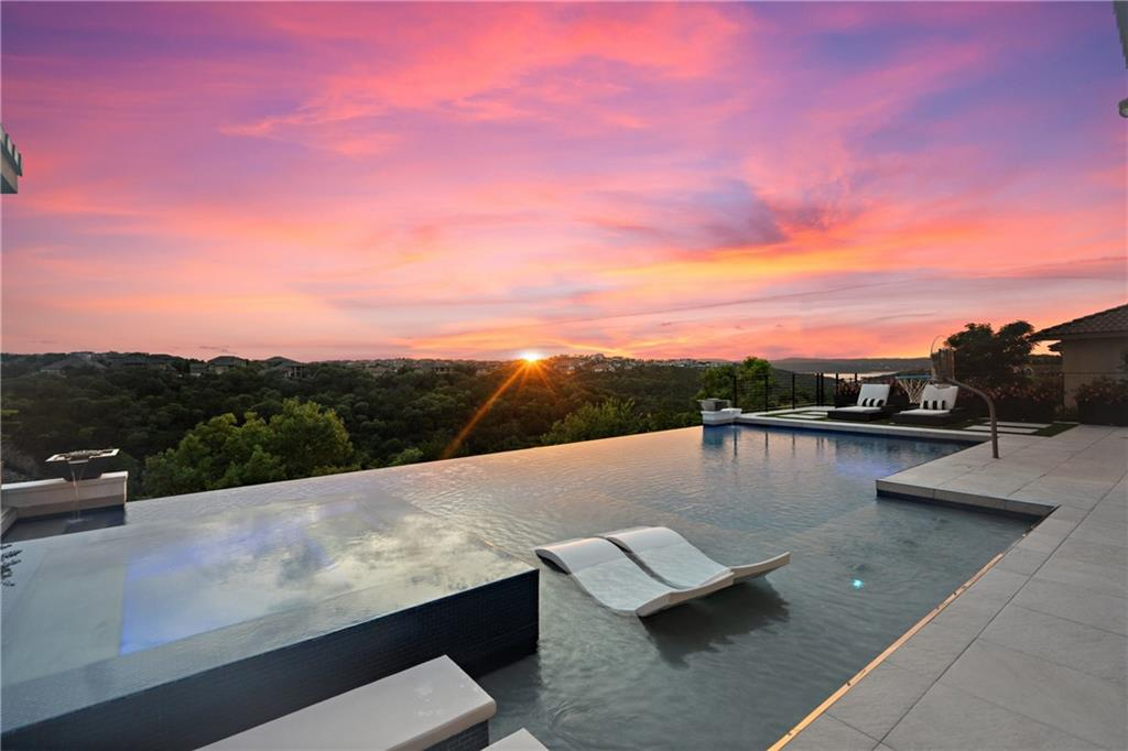 """Stunning modern retreat in The Bluffs at Rough Hollow with canyon & Lake Travis views. Jaw dropping white on white interior. Find exceptional attention to every detail in this entertainers dream. Luxury abounds throughout all finishes in this fantastic floor plan. Breathtaking 2 1/2 story living room opens to chef's kitchen & lofted game room with kids study. Tranquil 1st floor master suite boasts separate study, spa like bath and incredible boutique closet. Spacious guest suite down and 3 beds/2 baths up for privacy. Dream party patio featuring a gorgeous heated & chilled pool, spa, grill, cabana, waterfalls, fountains & fire pits. It's all here waiting for you - come live the """"rough life!"""""""