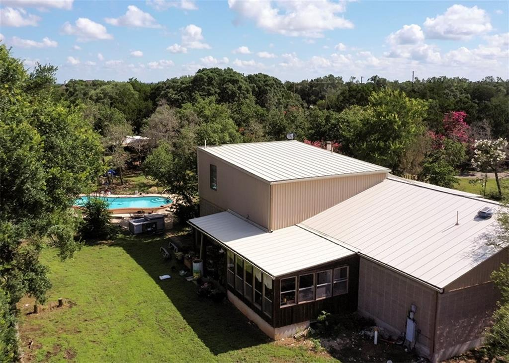 Located within one mile of highway 29 and highway 183, this 7.88 acre property has so many potential uses .  Located just one mile from highways 29 and 183, the property is ideally located close enough to major shopping, but is secluded enough to convey a peaceful quiet environment.  The main house features 2946 sf of living space and an in ground pool.  Also located on the property is a two story, two bed, two bath guest house, with kitchenette.  Adjacent to the guest house is a large pull through shop building.  A separate storage building is also located on the property.  The possibilities for this property are almost endless. A private compound, small home based business, or even possibly adding more structures, or homes may all be possibilities for this property.  The property is located in the county, but also in the ETJ.  Please note the property is comprised of two parcels: R324838, 5.88 and R324837, 2 acres,   of Liberty Hill.  Equipment outside does not convey with the property.  The owner is in the process of removing outside equipment, but may be willing to entertain separate offers for the outside equipment.