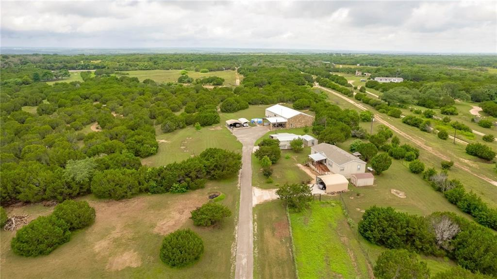"""Over 11 acres, 2 homes and outbuildings!  Sounds too good to be true...but here it is, in Liberty Hill.  This is a one of a kind, well manicured property. The property itself has: custom security gate with programmable access codes and key fobs,  above ground pool with stairs and a pool deck, basketball goal, 20x30 shop with a lean-to, new booster pump and a 500-gallon above ground storage tank, a new greenhouse, deer feeder and deer blind, large high-fenced garden, ATV/UTV trails around property, fields of bluebonnets in the springtime, and lots of wildlife on the back of the property as it backs up to a couple hundred uninhabited acres, and many trees planted over the past 5 years.  This listing is over 10 acres allowing you the freedom to hunt on the property. The main home provides you with: 4 bed, 4 bath, a loft, 2 pantries, a home office, all bedrooms have large walk-in closets, 26 ft high vaulted ceilings in the living room, two master suites (1 upstairs, 1 downstairs), and well insulated with 8""""+ thick walls giving you low power bills, even in the hot Texas summers.  The beautiful custom propane fireplace makes a great secondary heat source in the winter. The loft has a pool table, a 120"""" projector setup included, and its own full bathroom.  The second home has: 2 bed, 2 bath, a home office, laundry room, walk-in closets in all bedrooms, and a walk-in pantry.  Kitchen has modern appliances with a gas oven and cooktop.  There are front and back covered porches and the covered parking spot is near the house making for a short walk up the low angle ramp to the front deck.  The house also has a nice storage shed for your lawn mower and gardening tools.  Overall, this quiet property allows you to really feel like you're out in the country while still being close to the fast-growing town of Liberty Hill, Texas.  Easy access to Austin via the 183 toll-road makes for a quick commute and high speed internet is available for those that intend to work from home."""