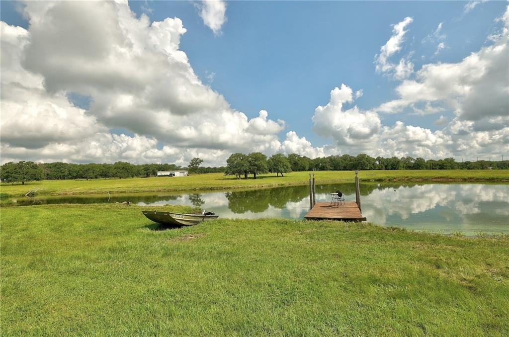 Rare opportunity to purchase a gorgeous acreage estate in the heart of Milam County less than an hour from Austin! This unique property sits on approximately 31.817 acres just outside of Rockdale city limits. Enjoy the peaceful quiet of country life while only being minutes from the conveniences of being close to town.  The acreage is some of the prettiest in Milam County with a beautiful blend of open spaces and wooded areas.  It is fully fenced and features 20+ pecan trees, countless sprawling oak trees, 2 stock ponds (one with a pier for fishing), orchard space, large garden area, built-in firepit, and a large patio space with a pergola & plenty of shade trees for relaxing and entertaining.  The main house is a 2300 square foot (approximately) home that underwent a major renovation in 2010 and offers an open floor plan with 3 bedrooms + office, 3 baths, 2 dining areas, 1 large living room, and a 3 car garage.  Features include abundant windows and natural light to soak in the panoramic views, engineered wood floors & hard tile (no carpet in the house), huge kitchen with center island & granite counters, walk-in pantry, and a gas fireplace with custom lighting options. The property also has a barndominium guest house (approximately 550 sq ft) with it's own kitchen, bathroom, & garage/storage space. In addition to that, there are also 2 large metal outbuildings ~ first is approx 1800 sq ft (half bath, office, 3 bays including a drive through, upstairs space for additional storage, and a wood heater) and the second is approx 2400 sq ft (3 bays with rollup doors). The main house is conveniently connected to city water/sewer/trash services and has a well for the sprinkler system for the yard.  The barndominium is on a separate well/septic system. Barndominium is currently leased out month-to-month. The opportunities for this property are endless & must be seen to be appreciated! Buyer to verify all information. Virtual Tour ~ https://www.seetheproperty.com/u/387512
