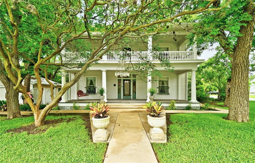 The Carrington House, located just off Main Street in Buda, Texas, a Greek Revival home built in 1909 is a show-stopper, with its unique historic design offering a nostalgic atmosphere unlike anything else in the area. Mature trees and landscaping enhance the charm of this lovely property. In addition to the 3,572 square foot home, the .52 acre lot features Buda's first school house, an outhouse and four covered porches! The character of this property is abundant! The regal entry off of 100 Cherry Street offers an impressive foyer providing access to the formal parlour featuring two fireplaces flanked with gorgeous detail, main bedroom also featuring an ornate fireplace and family living areas. Moving into the kitchen with its original farmhouse sink, you will find a sizable walk-in pantry and utility area to house all your wares which includes an authentic wooden rolling ladder to reach the higher shelves. The staircase leads to a second kitchen, main bedroom with ensuite, an additional bedroom, a full bathroom and access to the spacious porch to enjoy cocktails, board games, and a delightful tree-lined view of the neighborhood. The dormer on the third level is accessed through a private entry off the second floor hallway and is approximately 700 square feet of studio space filled with natural light, a full bathroom, kitchenette and laminate flooring. The covered patios and beautiful backyard leave plenty of room for outdoor enjoyment, with an oversized detached garage providing additional storage space. Live here and make the most of the highly rated Hays CISD schools, exceptional proximity to the Buda Amphitheater, City Park, Downtown Buda's Historic District that's filled to the brim with unique shops and restaurants. The historic Stagecoach Park is nearby with a pavilion, playground, and trails to explore. There is no shortage of ways to enjoy yourself in the area!