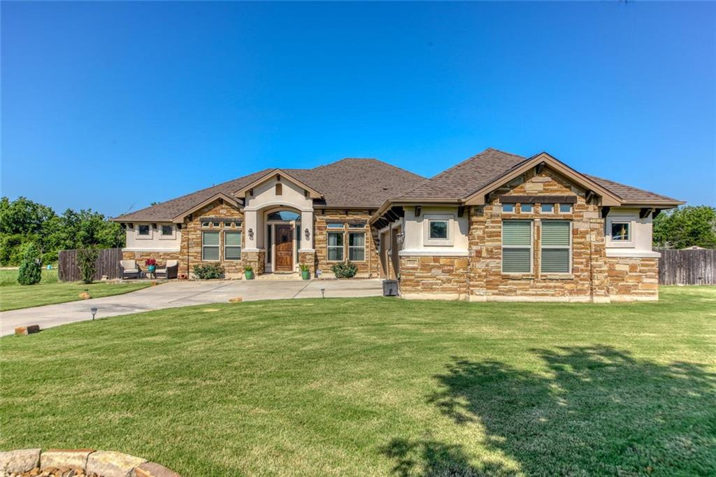 """Come live in the highly sought after community of Cierra Vista, one of Liberty Hill's custom acreage communities. This is a beautiful 3 bedroom, 2.5 bath, one story custom home located on a premium lot in a private cul-de-sac. This floorplan offers a ton of entertainment flexibility with an open concept: featuring a large great room with sliding glass doors, flex room/study with glass French doors, formal dining room, wet bar and gourmet """"u"""" shaped island with second dining area and tons of bar/countertop space. The kitchen has granite counter tops, glass tile backsplash and a stainless steel appliance package which includes a gourmet Bertazzoni Italian free standing oven. The main living space also features a master bedroom and a master bath with walk in shower and separate bathtub. There are two additional bedrooms and 1.5 baths on the opposite side of the house. The back yard on this home is an oasis featuring  an inground pool and spa, outdoor storage area, amazing covered patio with electronic solar shades. There are a ton of upgrades to this home: spray foam insulation, water softener with RO system to kitchen sink and fridge, mini-split in garage, 16x10 Tuff Shed in backyard conveys, 500 gallon underground propane tank, $35k+ in irrigation/landscaping to include an entire French drain system in the back yard, full gutters, tankless hot water heater and much more.  This home's roof was just replaced in June 2021. Conveniently located off Hwy 29/CR 200 in Liberty Hill, approx. 5-10 min from Hwy 183A."""