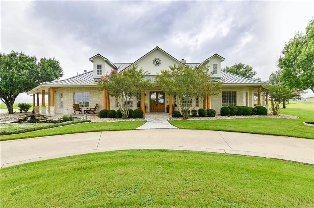 """Gorgeous 1 1/2 Story custom home, a combination of Texas Ranch and Colorado Ski Resort built on 12 beautiful acres and located on the north edge of Travis County! 5Beds/4Baths/4 1/2Baths/12 garages, plus a """"Car guy's man cave""""/workshop, barn, custom pool/hot tub with triple waterfalls, 2 fully stocked ponds and a large Koi pond.  Lots of river stone, oak trims & crown moldings, pecan cabinets and mesquite floors throughout the home. Large family room with 17' vaulted tongue & groove ceiling with massive beams reclaimed from a 125 yrs old barn complement the floor to ceiling river rock fireplace, built-in bookcases and wet bar with wine cooler. Lg wrap around the front porch accented by cedar log/stone columns lead you to the custom Koi pond. Koi fish will not convey*Ponds are fully stocked with Bass, Catfish & Bluegill and a floating dock with benches for seating or fishing! Country living at its best & just a short way away from Austin, Round Rock, Eateries, Shopping, Hospitals & Access roads. Please see attached property overview!"""
