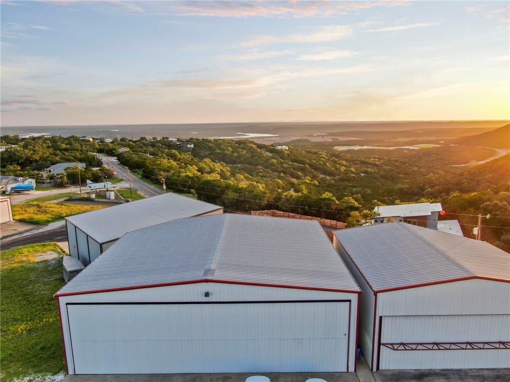 This unique property is zoned C-4 multi-use commercial and allows for residential, manufacturing, retail and/or office use. The 5,000 (+/-) sq foot airport hanger can accommodate multiple airplanes at one time. The top of the line electric bi-fold doors open up to allow for airplanes up to 15 feet in height.   In addition to the 1st floor hanger, there is a 2300 (+/-) sq foot apartment on the 2nd story.  The apartment has 2 primary bedrooms, each with en-suite bathrooms. In addition to that, there are 2 other bedrooms with built-in bunk beds that share a full bath.  Enjoy epic Hill Country and lake Travis views and sunsets from both the 1st floor hanger and the 2nd floor apartment balcony.  This rare offering is not to be missed!  INTERIOR PHOTOS ARE AVAILABLE UPON REQUEST