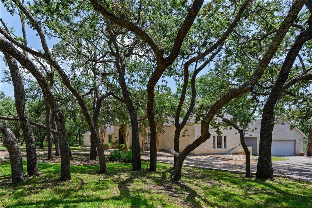 Enjoy the Privilege of Privacy in this beautiful horse community of Saddletree Ranch. Nestled on 1.66 acres under a tall oak canopy in Texas Hill Country. Saddletree Ranch offers large homesteads, appealing amenities, horses are welcome and a location that is convenient to shopping, dining & the quaint town of Dripping Springs. Tree lined circle drive sets the tone with landscaped grounds to this enchanting custom home.  Automobile enthusiasts or hobbyists will LOVE this 2100 square foot shop which is insulated, has 220V electric outlets and has been plumbed for a bath.  Inside you will find 4 bedrooms, 3 full baths, 1 powder room, and 2 living areas. With 2 spacious bedrooms on the main level each have en-suite baths this home offers guests their own private retreat. Warm wood flooring flows gracefully throughout the lower level with tall ceilings and large windows that invite wonderful natural light. Bright country kitchen has rich stone flooring, is open to the family room with a breakfast bar, sunny breakfast nook and with tree filled windows. Private Owners retreat grants lovely views to the fenced backyard and a spa style bath with dual vanities, walk-in shower, a deep soaking tub plus his and her closets. This floorplan is ideal for entertaining with formal dining open to an impressive family room with fireplace.  Brand new AC for upper level which has 2 quaint bedrooms, a large, shared bath and loft gathering area. Treat your senses when you step outside to a sprawling flagstone & pergola covered living space with Summer Kitchen. This outdoor living flows to a sprawling backyard which is enveloped in tall vegetation offering nice privacy. Known as the Wedding Capitol, Dripping Springs has vineyards and breweries  peppered throughout the sweeping vistas as well as natural areas offering hiking and mountain bike riding or rock climbing.  Ideal location for weekend adventurers. *24 hr notice. Buyer must verify sq footage*