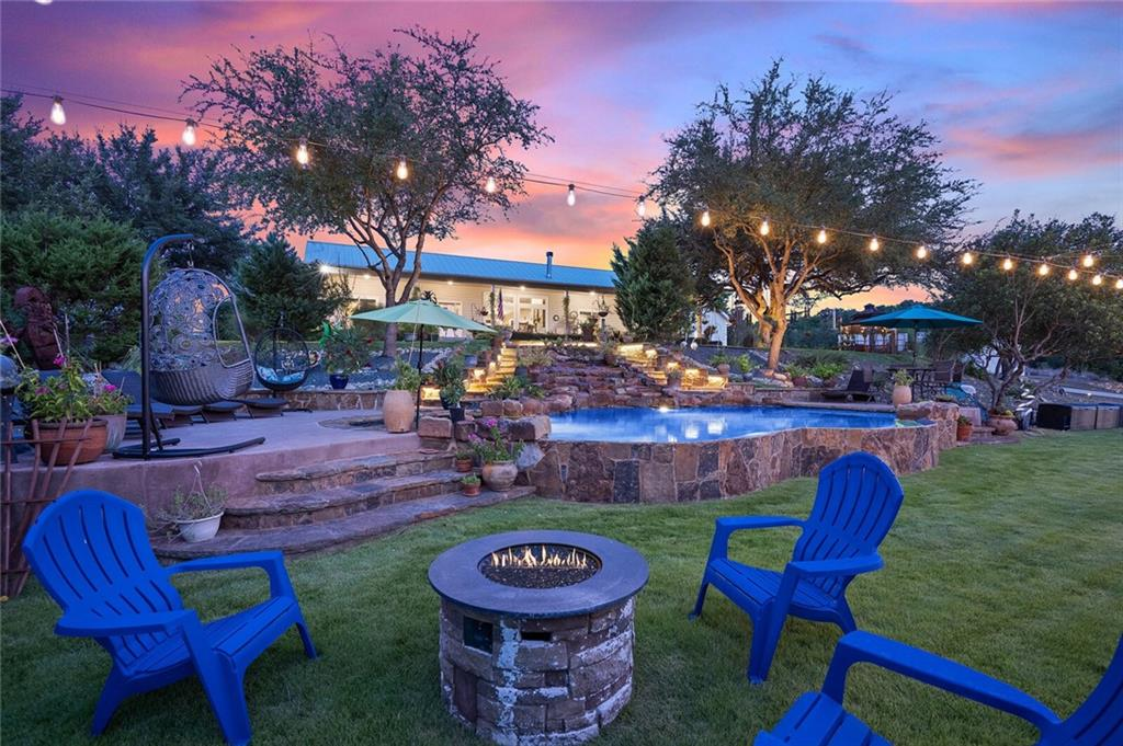 Welcome to 4607 R O Drive – much more than a gentleman's ranch: a little slice of heaven in the famous Texas hill country. This amazing paradise is perched high on a ridge offering incredible panoramic views & gentle breezes. The property is gated with 10 acres of unrestricted land. There are 3 dwellings & several storage buildings plus plenty of rolling wooded areas for additional development. The Main house is a beautiful ranch style home in the center of it all with a side by side covered front porch pointing North West to take full advantage of the incredible sunset views. The interior consists of 4 Bedrooms (2 of which are full suites), 3 full bathrooms, an open living/dining/kitchen area in the heart of the home plus a large laundry & pantry. The covered back patio of the main house overlooks the fenced yard which opens to the fire pit, studio & entertainment house. Inside the 2 story studio is a large living area on the 1st floor with a bedroom, full bathroom & small living room upstairs. The entertainment house is amazing – it has 2 huge rooms used as a game room & media room + a half bath. Above it is a full guest suite offering a living, dining, kitchen, bedroom & full bathroom. The pool has a cascading waterfall flowing from the upper yard at the front of the main house down to 2 tanning ledges. There's also a gazebo, huge fenced in garden, 1 car garage/storage shed, RV garage with a lofted office, oversized 6 car carport & a large storage trailer.  On well, septic, solar & propane. This property is truly one of a kind and the possibilities are endless.