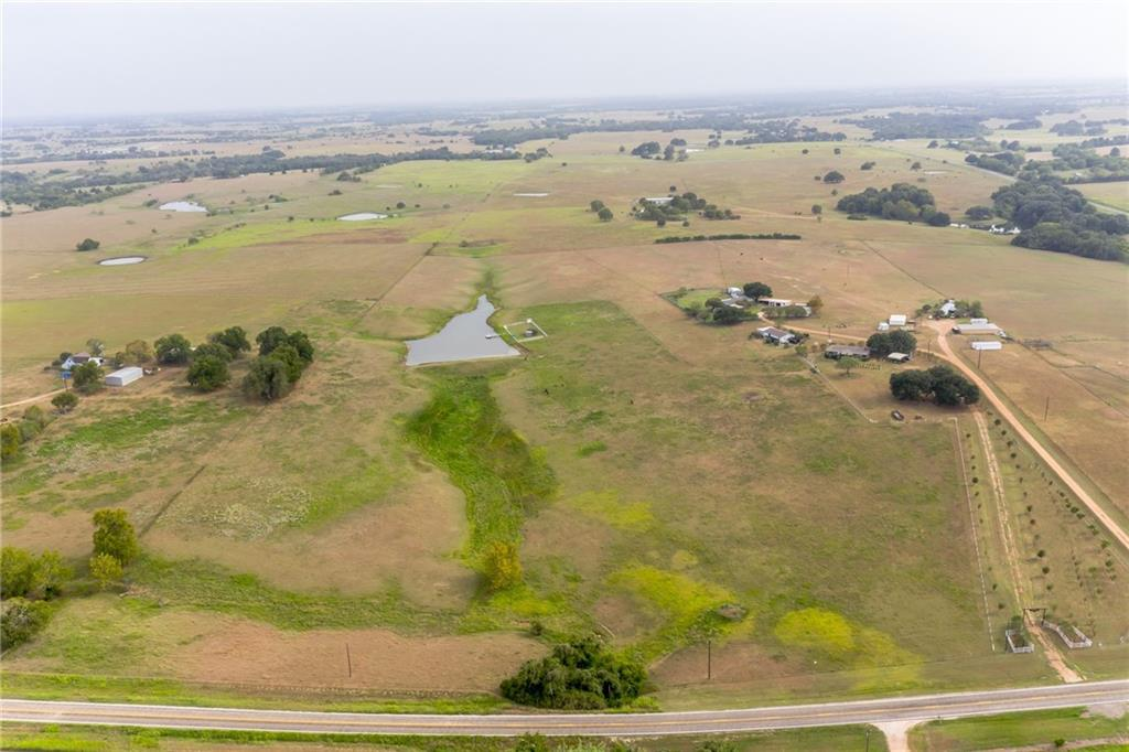 2016 built 3/2 country home at 425 ft altitude providing panoramic views of the beautiful surrounding countryside! One acre spring-fed, stocked pond with floating dock and screen shaded picnic/sitting 12x24 gazebo with fenced grassy surround. Home has awesome 2260 SF covered porches for relaxing in the country breeze. 480 SF TX style carport-roof only. Playscape area for kids and outdoor party area with firepit all shaded by large live oaks. Property is wonderfully landscaped including a newly planted, producing, fruit orchard! Property has new water well but also a county water line at front of property.  State maintained paved road frontage with low volume traffic. Central in Ammansville area, 15 min. to I-10, Hwy 71, La Grange & Schulenburg.