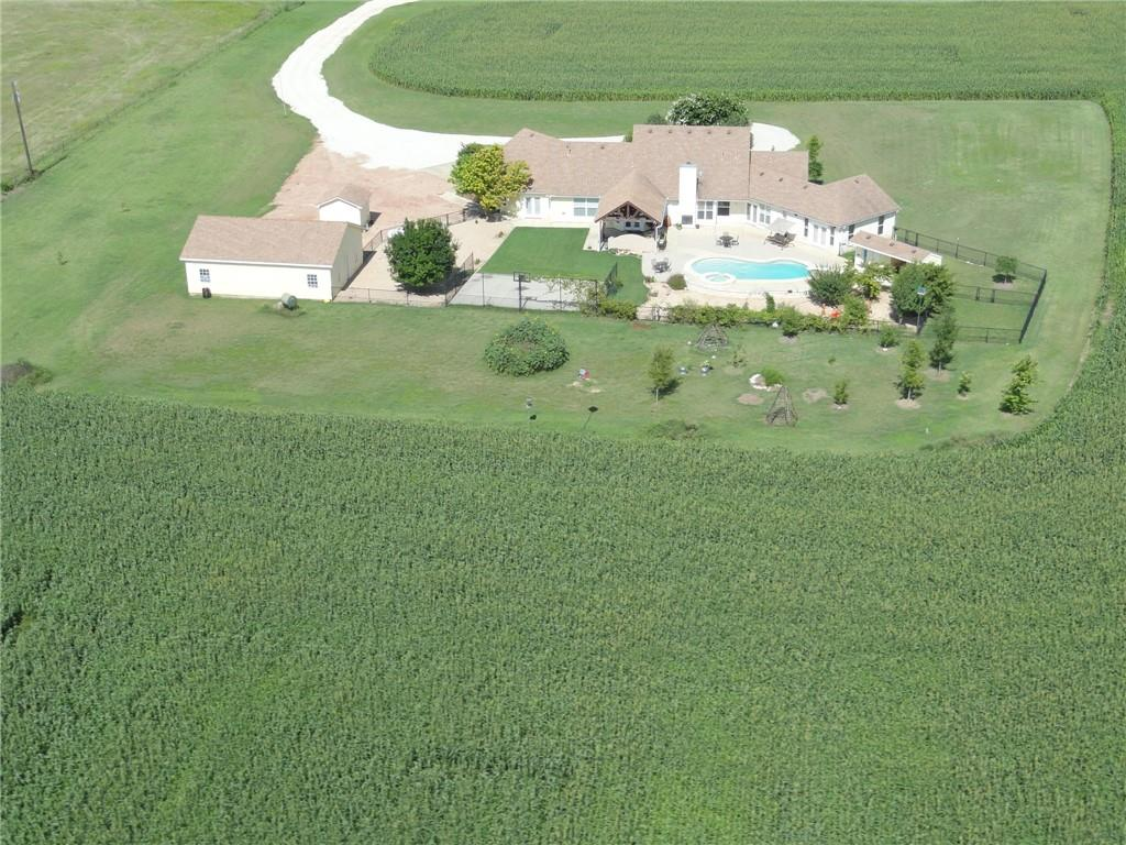 Custom stone home on 12.5 acres.  Front and back porches.  Two master bedrooms.  4 bdrms, 3 baths, 2 half baths, 3 car attached garage. Barn/shop 1312 sf with electric and work shop. Swimming pool with jacuzzi. Outside shower/bath/sauna. Sprinklered yard w well water. Outside kitchen and entertainment area. Work-out room off master suite. Gourmet kitchen w/ breakfast bar.  Large breakfast area. 2 dinings. Granite counters. Tile backsplash. Solid hardwood floors in entry family, formal dining area. Crn mldg family and dining