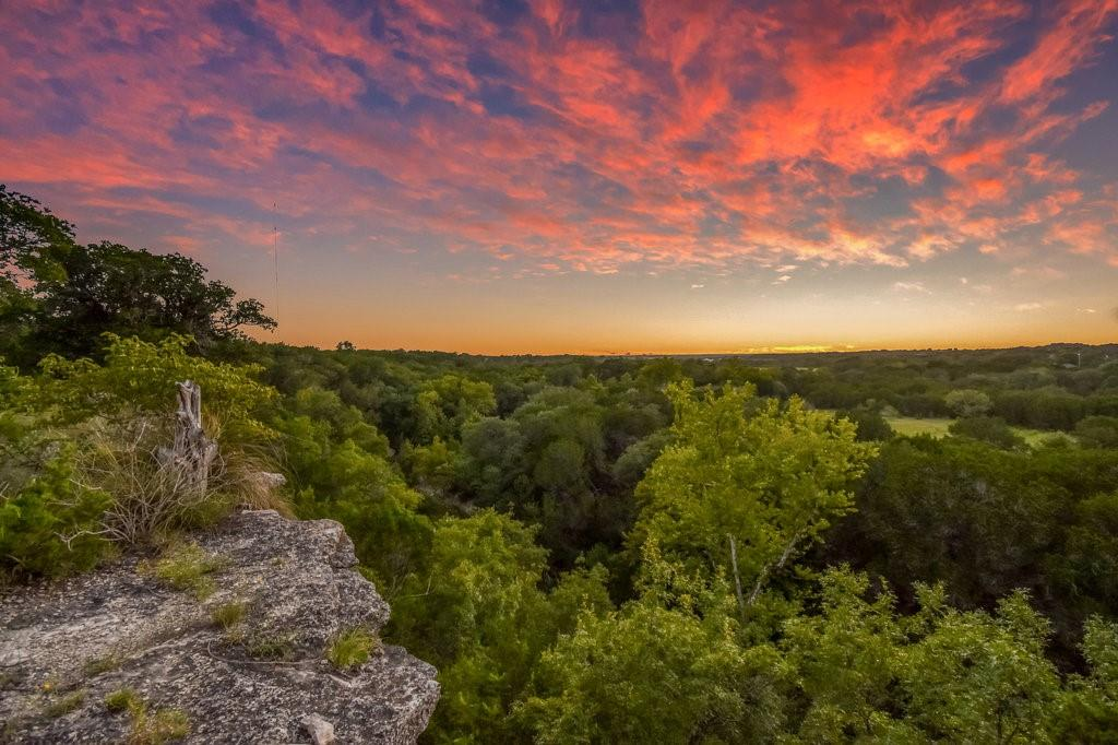 Enjoy 76 Acres of true Hill Country land, from the views off the bluff to the babbling creek below, this property is a dream.  Conveniently located an hour from Downtown Austin providing you with a close opportunity to escape the busy life.  Upon this 76 acres you will enjoy nature at it's finest, hunting, atv cruising, enjoying the 1 mile stretch of Bear Creek that runs through the property, and sunsets that go on for days. History is rich on this land, generational owned property with stories of ancient Indian camps, proven with the numerous arrow heads found through out the property, along with the 50+ year old pecan trees planted by owners from generations past.  You also have a 40x60 Barndo with 3 bedrooms, 2 full baths and a 750 sqft shop/garage area.  There is another 30x40 workshop plumbed with a 1/2 bath and a covered carport on one side to park all your big boy toys and 2 RV Hookups.  Schedule a guided tour today for your chance to own a piece of the Hill Country.