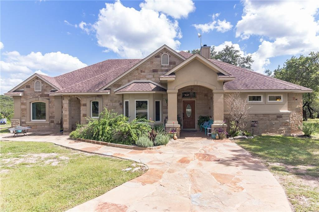"""THIS CUSTOM BUILT 100% STONE/STUCCO SINGLE STORY HOME ON 6 ACRES (To be sub-divided out of 13.18 acres) IS SURROUNDED BY NATURE & HILL COUNTRY VIEWS! Recently added Andersen windows allow for an abundance of natural light inside while providing great Hill Country views out of almost every room in the home! The open formal living & dining area leads into the kitchen w/breakfast area & family room. The well appointed kitchen offers granite counters, stainless appliances, pantry & loads of storage space. The spacious primary suite has tray ceilings, double vanity, walk-in shower, built-in cabinets, & an exterior door to access the rear patio. There are three additional guest beds on the opposite side of the home (two w/a Jack & Jill bath). The 30'x50' garage/barn w/large sliding doors on each end is perfect for storing your cars, boat, lawn equipment and more. VERY LIGHT RESTRICTIONS ALLOW FOR COMMERCIAL USE & WOULD BE IDEAL FOR ANYONE WANTING TO HAVE THEIR HOME & BUSINESS ON THE SAME PROPERTY. Recent updates include windows, limestone walkway & side patio, new granite counters, water heaters, A/C, and more. Please note that taxes and assessed tax value are estimates as this home/6 acres is""""to be"""" subdivided out of 13.18 acres."""