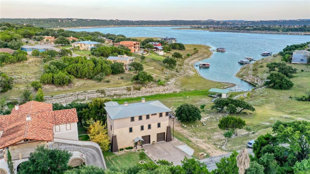 Live a lake lifestyle on park like setting overlooking the water where the breeze is always amazing! VRBO's and AirBnB's WELCOME! Elevator to access all the levels for gorgeous views of the Lake Travis sunsets! The middle floor has a media room, ***2nd kitchen***, 2 bedrooms, a bath, and additional game room. The top floor is the main living level with a master bedroom separated from 2 other bedrooms, a kitchen and living area. 2 balconies and a covered patio expand the back and side of the house for ultimate entertainment. Fire pit area and oversized, 8-person hot tub convey! Boat dock, jet ski slips and jet ski negotiable. Oversized garage for all your water toys-even room for a workshop (some wire shelving will stay)! New features include rock on the side of the home, solar screens, flooring and wall color, new carpet, bench seating for kitchen table, *auto shades*, kitchen cabinetry and concrete addition for more parking! There is so much wildlife in this area and great views from everywhere.