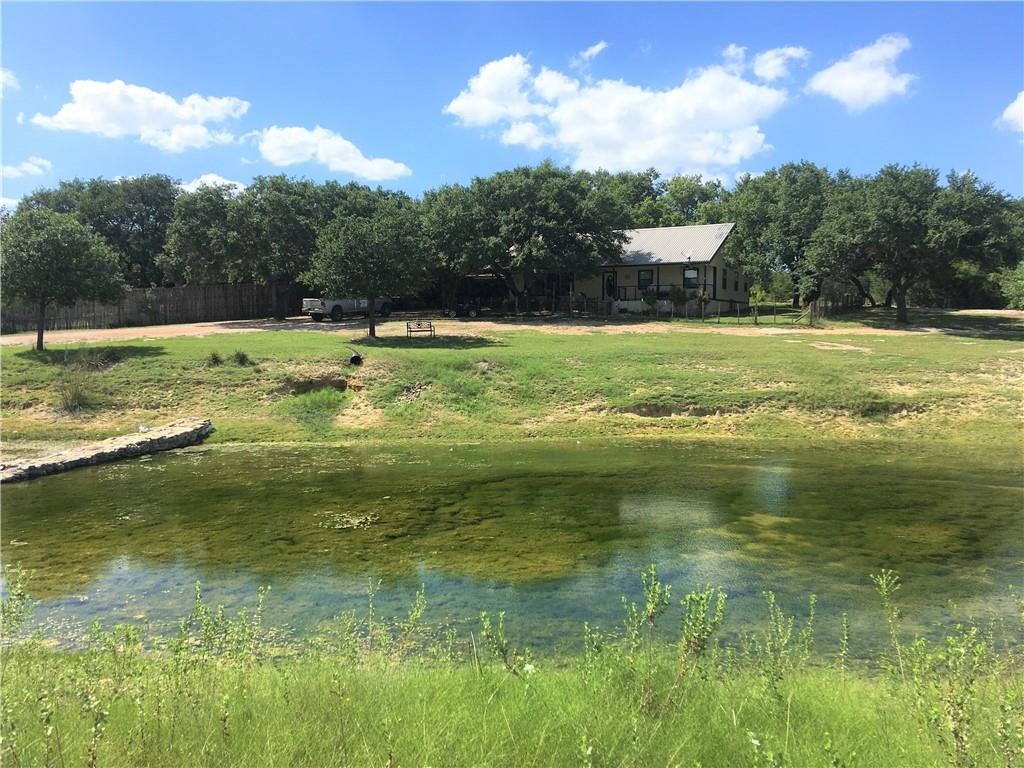 3/2 Ranch Style Home (1716sqft)on 4 unrestricted acres overlooking stock pond. It also has a like new 2019 3/2 mobile home(1976sqft) as guest quarters, barn, shop with A/C and well pump house building. The main house has a large front porch to enjoy the beautiful hill country views from the porch swing. Yard is shaded and fenced for dogs along with covered parking. Plenty of privacy as it backs up to large ranch and perimeter is all high fenced. The Main House has a nice wood burning natural stone fireplace that was well used and appreciated during the big freeze of 2021. Master bedroom is large with his and hers walk in closets. Massive Oak Trees shade the house and several others provide plenty of shade for animals. Barn has turnout pen and plenty of room for horses, hay, feed, tractors, 4 wheelers, and 4H/FFA show animals. Solar powered entry gate. Convenient location between Dripping Springs and Johnson City just 1.3 miles from the intersection of Hwy 290 and Hwy 281 make it easy to get to Austin, San Antonio, Fredericksburg, Marble Falls.