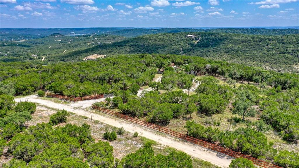 Gorgeous piece of land that has had a lot of TLC in the past few years.  Approx. 5 Acres of level area on top of the mountain with clearings cut with views of the hill country. Numerous improvements to the property as well as a 2012 Honda MUV700 4x4 utility cart and 2019 Keystone Springdale 26' Travel Trailer (never been towed) among other items  that convey with property. Build your beautiful estate home or just have a weekend get away, this property is secluded and private! Close to Jonestown and Cedar Park! Seller will give Buyer a $15,000 allowance towards installation of septic system.