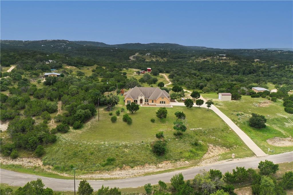 Take the scenic Hill Country drive down famously fun Fitzhugh road, and find a curvy path with few homes and vistas everywhere. Welcome to Lost Valley and the 11+ acres perched high above it. The primary home towers on the hill at the front of the property, offering views across the valley and towards the north and west for sunsets. The main house has 4 bedrooms, 3 and a half bathrooms, a study, 2 dining areas, 2 living areas, and a large laundry room all on a single story. Continue down the gently sloping driveway, passing the toy garage for your ATVs, two small ponds (wet weather), a solar-lit sport court (basketball/pickle ball), majestic oaks sheltering a fort/treehouse, and follow the curve to reach the guest house and barn with workshop at the far end of the property.  The guest house is a 2017 manufactured home of 3 bedrooms, and 2 baths with its own septic and utilities. With two RV hookups you're a capable and ready host. Entertain from multiple locations — the main house has a covered outdoor kitchen and living area with a fireplace, half bath, TV, food prep area, built in gas grill and refrigerator. Dripping Springs schools, lifestyle, and room to roam.  If you are wondering how far amenities and necessities are from the property, here are a few commonly asked locations: distance to HEB grocery store: 13.1 miles; distance to closest gas station: 10.1 miles; distance to fire department: 12.3 miles; distance to ER: 23.1 miles; distance to Walnut Springs Elementary School: 14.5 miles; distance to Dripping Springs Middle School: 10.8 miles; distance to Dripping Springs High School: 11.9 miles.  School bus picks up at driveway for all schools!  Grocery delivery is also available to this property.