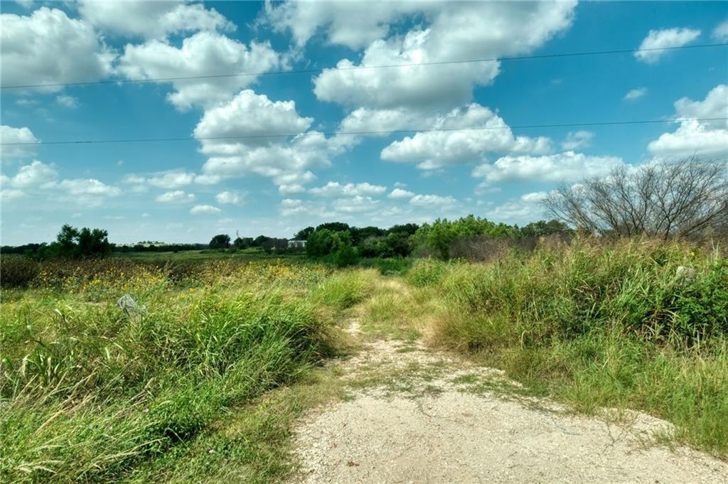 -Rare 62.62 acres of rolling scenery with a creek at the bottom of the hill and a gorgeous place for a homesite at the top.  Panoramic view-pasture is already planted in corn-There is some junk and falling down mobile homes which will be removed prior to closing. There is probably an old septic system there but no idea if its usable.  2 Manville water meters on the property.
