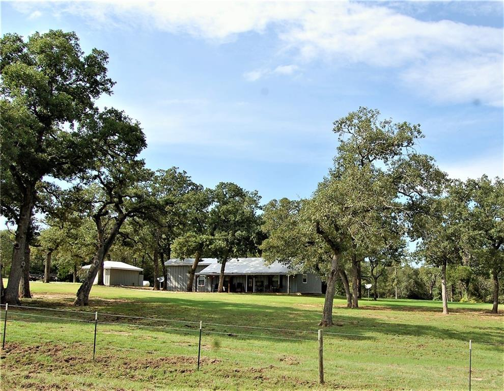"""COME AND SEE THIS BEAUTIFUL PROPERTY on the Williamson/Milam/Lee county line. This 96 acre beauty is a hidden treasure at the fork of two wet weather creeks.  This 2/2 well maintained home is a cabin-like gem that sits in a cluster of oak trees.  The kitchen/dining/living are in the front of the home.  The kitchen is appointed with stainless steel appliances, quartz countertop, farm sink, gas stovetop and built-in microwave and oven.  It has a large eat-at island for your entertaining.  Take your pick of the front or back porch to relax, unwind and watch for wildlife. The property has electricity but also has a Generac that can handle all of the improvements on this property.  This Generac, water well, and septic allows you go totally OFF THE GRID. The master bath suite contains double sinks, a large double head walk in shower, California closet, washer dryer and office area. Bring all of your """"toys"""", RV and/or equipment and shelter in the new 50x60x18 insulated shop.   From this home the property rolls down into a wet weather creek and back up to a breathtaking hay pasture where you can enjoy sunsets.  The creek meanders through the property to a serene pecan bottom with many awesome pecan trees.  There are two water purifying systems, tankless hot water heater, sprinkler systems, and irrigation for the pecan grove. This property would be great for a homesite or hunting or recreational get-away.  Lots of wildlife including, whitetail deer.  A great place for the whole family including the furry family members!"""