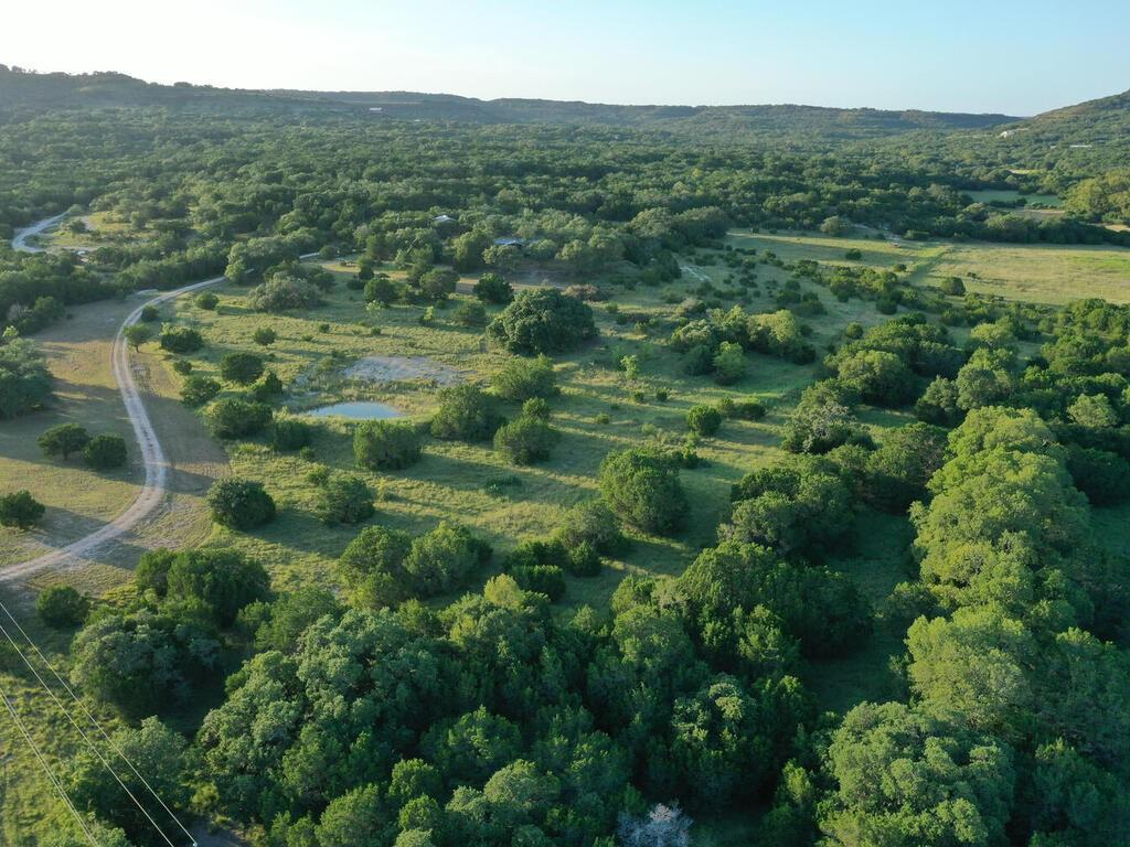 Boasting amazing views of the surrounding Hill Country all the way to the Devil's Backbone, this Blanco County property is the perfect spot to call home. The driveway is directly off of FM 2325 making it accessible to all the Hill Country has to offer: 13 minutes to Blanco, 18 minutes to Wimberley, 25 minutes to Dripping Springs, 55 minutes to Fredericksburg, a little over an hour to San Antonio and 1 hour to Austin!   An improved rock driveway will take you to the highest point on the property where a completely redone 910 Sq.ft manufactured home sits with a distinct custom Hill Country cabin feel to it. The home has new floors, ceilings, fixtures and a bunch of character. Next to the house sits a shop with 2 roll up doors, electricity and pop up windows for air flow. On the back side of the shop is an overhang for vehicles or could be used as a shelter for horses and other animals if desired.   This property has countless build sites, all with their own unique views. The property is scattered with cedars and large oak trees. In fact, the second oldest oak tree in Blanco County lives just below the house. There is a small stock tank towards the front of the property and the property is terraced to limit the effects of runoff. For the history buffs, this property has water troughs and a rock stagecoach unloading ramp that reportedly date back to the 1800's during the Peyton Colony days.   If you are looking for a property that has endless views, good access to towns, water, electricity and a house, come take a look at this place!  Website for the POA: hillcountryranches.net