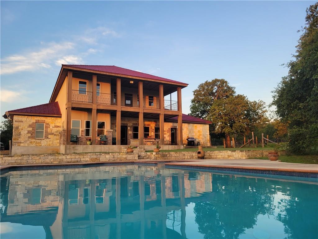 Located less than a twenty minute drive to Austin, a winding tree lined asphalt drive leads to this private 13+ acre country estate with stunning views. Located in the highly desirable Texas Hill Country, this home boasts an ideal location only 3 miles from The Salt Lick and Driftwood Golf Club. This lovely 3-bedroom home features a master bedroom suite complete with an added bonus fitness room. A large living area opens to a custom kitchen featuring knotty alder cabinets and custom rock work. Work from home in one of the two office spaces. Upstairs features a large entertainment room perfect for get-togethers. A large pool with a pool house, expansive outdoor porches and balconies are just a few other highlights of this home. The property is covered with mature oak trees and features plenty of privacy and unforgettable views as it backs to a 200 acre ranch. A separate park-like fenced-in side yard connects to the backyard/pool area. The property is ag exempt and stretches to a creek in the back.