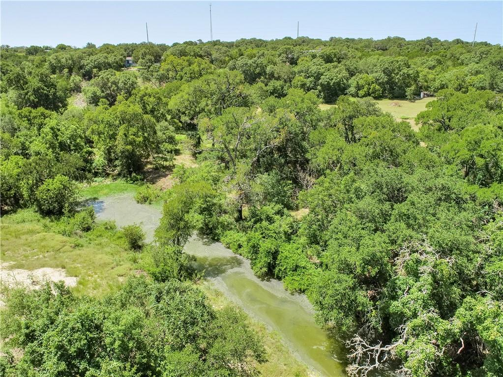 If you have been looking for just the right piece of property to build your home or want beautiful country living in the home on site, well look no further.  Welcome to these 11 acres, in the amazing LHISD, and surround yourself with true Texas living. The main features of this property are the amazing Hill Country views and the vast Oak Groves, including some impressive Heritage Oaks.  Abundant wildlife are drawn in from the stock pond and also Clear Creek, which runs along the back property line. For the cooler months, relax on the hilltop at the fire-pit and enjoy the views of Pilots Knob. During warmer seasons the wild flowers on the meadow and fireflies are a sight to behold. If you need a place to live while you build, well you are in luck.  There is a really nice four-bedroom, 2,432 square foot house, with three full bathrooms.  On top of this, the property has a well, septic, electricity at 2 locations and is fully fenced with an electric gate.  Cross fencing is in place and ready for horses.  There is an old barn, storage building, chicken coop and a playscape. Come and explore all this place has to offer and make your Texas dream come true.