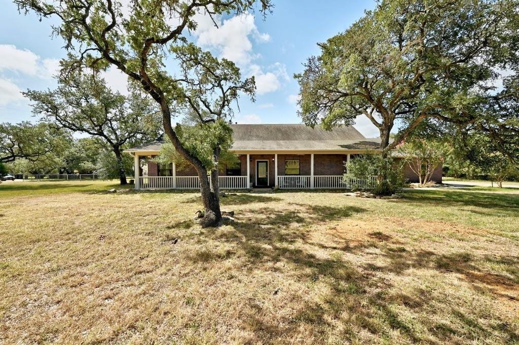 Charming custom built home nestled in 2 acres surrounded by fifty plus live oak trees and an idyllic wrap around porch. Home features hard wood floors in the living spaces and spacious living area. Create a home office or host fabulous dinners in the dining/flex room.  Experience all the charm and privacy of the country while only a quick commute away from Austin via the 45 Toll and minutes to downtown Buda.  This maintained home has been lovingly cared for. There is room for growth by adding to the existing home or adding a separate structure (deed restrictions to be verified by buyer).  Private, fenced-in backyard and located in the Oak Forest neighborhood dead-ending to a cul de sac.  Home is zoned to the top rated Buda elementary school.  Starbucks and CVS are minutes away.  Green Acres on the cusp of city life!