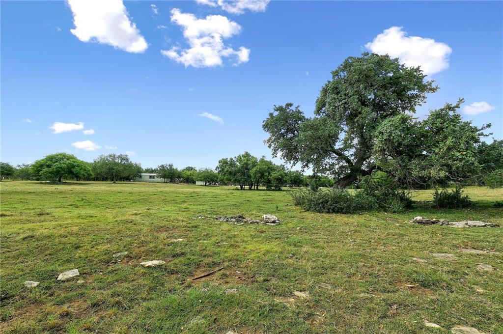 Your little slice of heaven awaits you on this 10+/- unrestricted acres with long distance hill country views! No HOA! This property has it all!  Fully fenced (2 sides are high fenced) and nestled next to an exotic game ranch, this property has an abundance of privacy. An electronic gate and two livestock watering tanks are located at the front of the property and a well-maintained gravel road leading to the homesite is where you will find the heart of the property; a remodeled 3/2 manufactured home with metal roof, courtyard with above ground pool, fenced garden area with raised bed irrigation with a custom designed and built chick coop.  Equipped with electricity, septic and well.