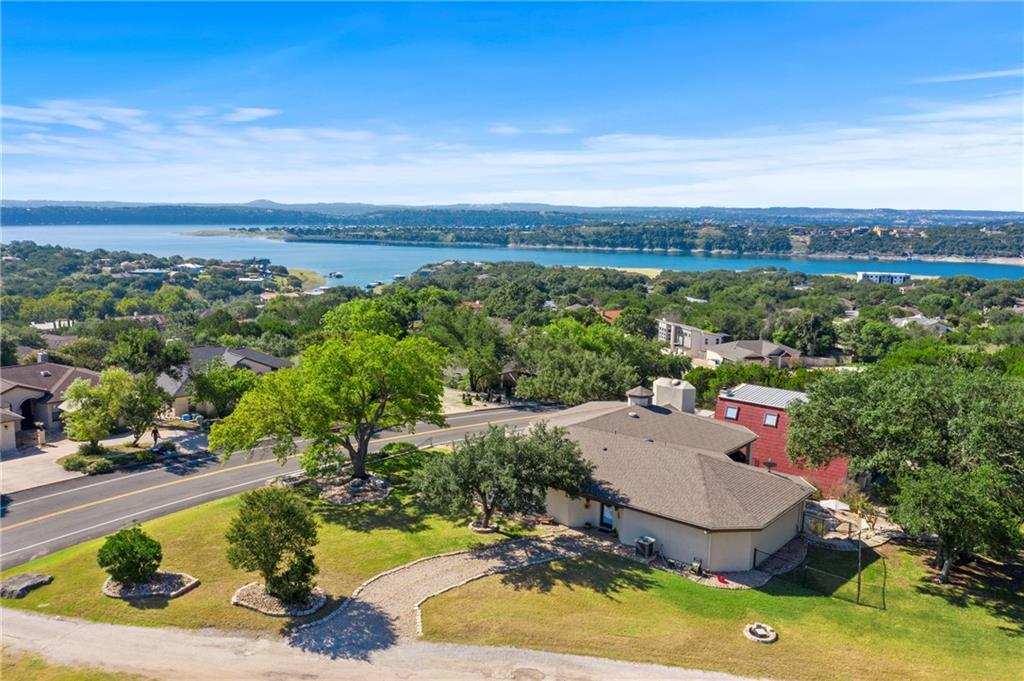 If you know Lago Vista, you know it's one of the Texas Hill Country's premier Lakeside Resort Communities on the North end of Lake Travis. Minutes from Cedar Park, Austin, and the Lake LBJ communities of Horseshoe Bay and Marble Falls, this Custom home was originally built for the former Mayor of Lago Vista in 1983. Numerous updates and enhancements made by current owners have created a wonderful retreat for those looking for a destination home that is ready for investment buyers, retirees, or even 2nd home vacationers. The home sits atop a hill, providing picturesque views of the lake, and butting up to the #1 tee box of the frisbee golf/golf course, events center club house, and The Grille Restaurant. There are 350 acres of recreational amenities, including 9 parks, 6 party pavilions, 5 playgrounds, 4 boat ramps, a marina, RV campground, swimming pool, and so much more. Holy cow, are you salivating yet? This 2 story home boasts of an enormous great room with beautiful rock fireplace, opening to a cool and comfortable front viewing porch, and lined with picture windows for views of the lake and golf course. The wrap around upper balcony on the home's backside overlooks a huge courtyard surrounded by rock features, landscaping and 2 Fire pit areas, all perfect for relaxing or hosting parties and backyard barbecues. 2 Master suites/full baths on the main level and an in-law suite/full bath, den and office downstairs, make this a perfect personal or vacation home you must come see before it's too late