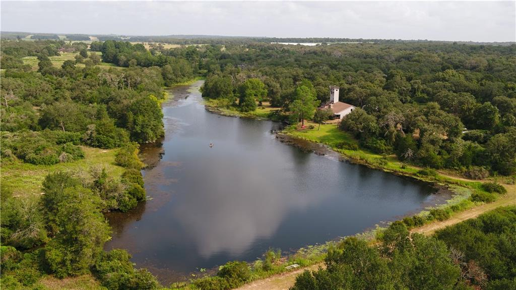 Large private lakes are hard to find. This secluded property offers just that: a large +/- 5 acre lake that is ready to enjoy with approximately 1/2 mile of shoreline! This lake is clear, deep and full of fish to catch. A dock is in place and ready to relax on or catch fish from as well.   This 69.46 acre property is mostly wooded with tall oaks and some pines that line the lake area. The rear of the property is accessed via a road over the dam and is great for hunting, shooting, riding horses or ATV's. Several trails are in place, and there is plenty of blank canvas for more homes, hunting spots or trails if desired. Perimeter fencing is in place.  A large, +/-3,400 square foot home site just on the lakes edge. It is spacious and would be a great home for a permanent residence, weekend getaway or lodge-type guest facilities. This home was built in the mid 1980's and has 4 bedrooms on the lower level that are all large with full baths on each room. A large back porch offers plenty of shade to relax on. The second story has two bedrooms with a half bath on each. A centrally located kitchen is the hub of the home and there is a dining area as well. The second floor is accessed by a spiral staircase and has an awesome open-type walkway to each side that overlooks the living and dining areas! The most unique trait of the home is a tower that soars some 50 feet in the air! A new roof and windows have been put in recently.  Next to the home is a 5-car garage with ample room for storage, vehicles or ATV's. Above this garage is an extra living area with a living room, kitchen, one bedroom and one bathroom. A metal shop is in place as well for tools and additional equipment.   This property has private road access via PR 7050, which comes off of CR 375. This leads to the ultimate privacy, and best of all: the private road dead ends into this property. Located just 1.25 miles off of HWY 79 and approximately 45 min from B/CS and 1hr from the I-35 corridor.