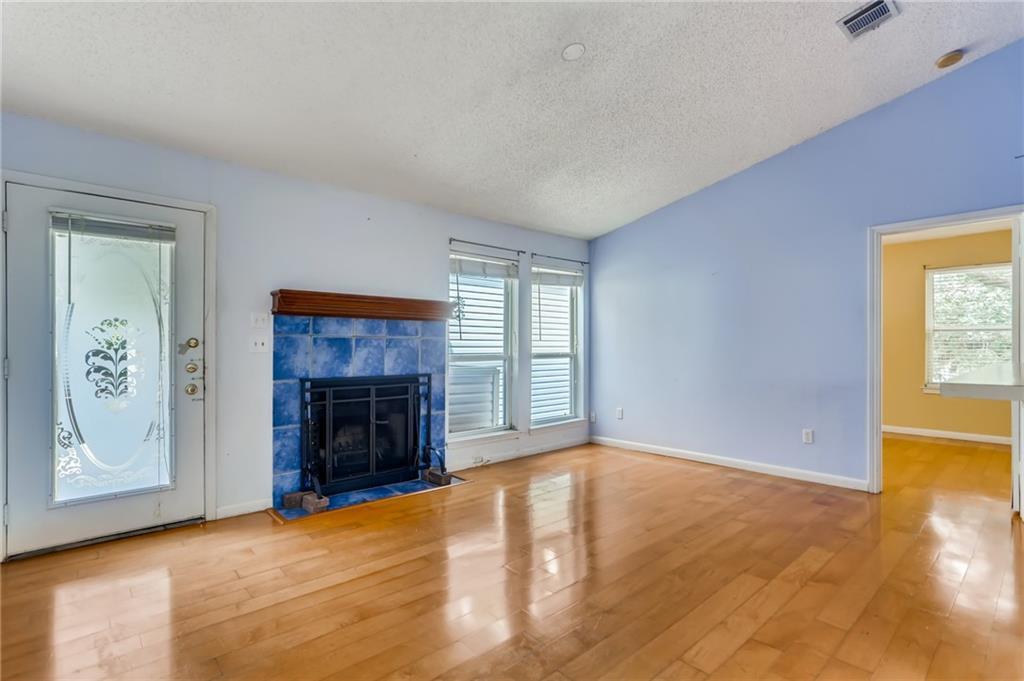 Living boasts vaulted ceiling, wood floors, wood-burning fireplace and abundant natural light.